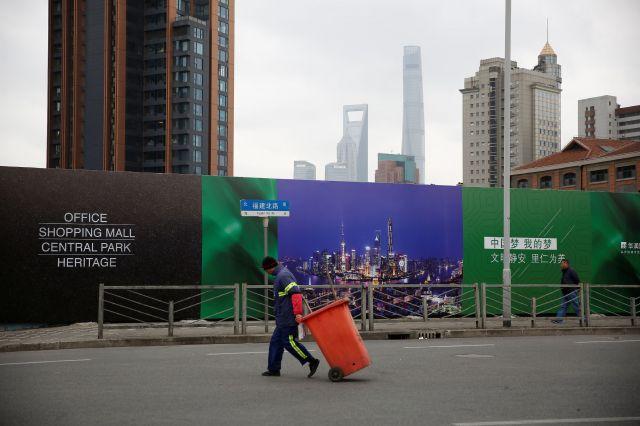 ゴミ箱を引っ張る清掃員=2017年2月、上海