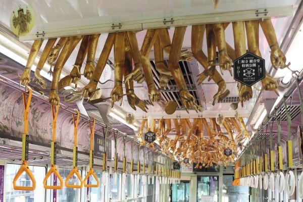 嵐電の「観音電車」に取り付けられた中刷り広告。千手観音菩薩立像の手が、天井から無数にぶら下がっているように見えます