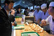 国際メディアセンター(IMC)内のダイニング脇の「ライブキッチン」では、たこ焼きの実演があり、多くの外国人記者が注目していた=6月28日、大阪市、鬼原民幸撮影