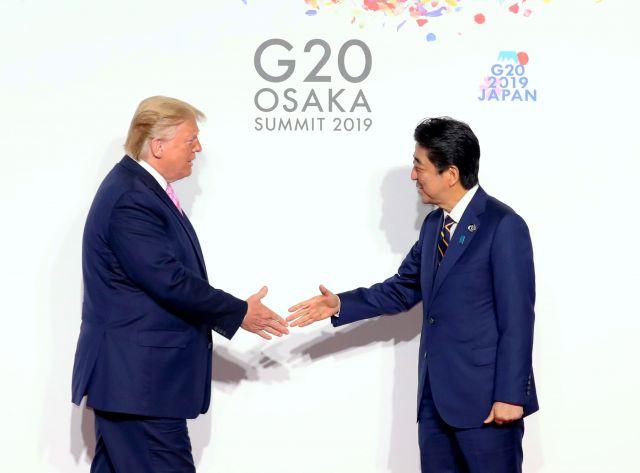 トランプ米大統領(左)を出迎える安倍晋三首相=6月28日、大阪市住之江区、代表撮影