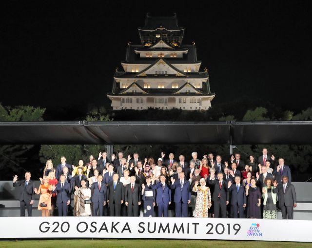 大阪城を背に、集合写真に納まる各国首脳と配偶者ら=6月28日、大阪市中央区、代表撮影