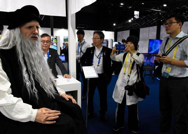 人工知能(AI)やロボット技術を紹介するブースも。人間そっくりのロボット(左)に注目が集まっていた=6月28日、大阪市、鬼原民幸撮影