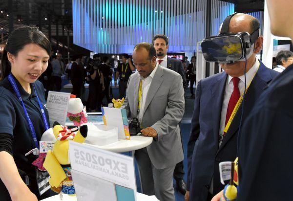 ダイニングの手前に設けられた企業ブースでは、VR(仮想現実)体験をする外国人記者の姿も=6月28日、大阪市、鬼原民幸撮影