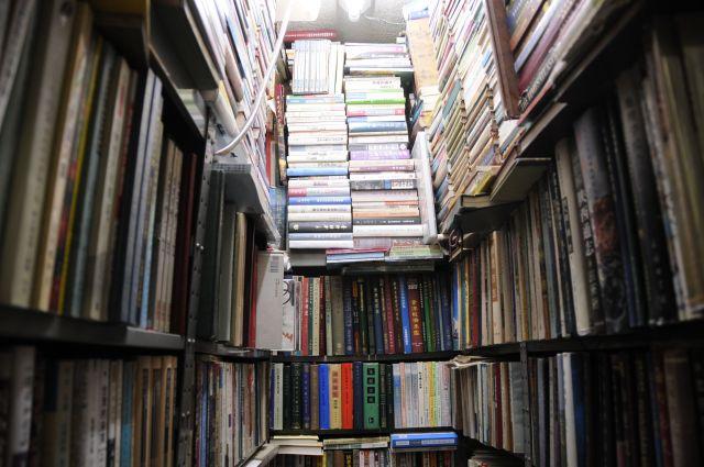 店のあらゆる空間に隙間なく積み上げられた本。こちらに通って40年近くになるという常連の一人は「いくら通っても、3分の1はまったくなんの本か分からない」と話す=今村優莉撮影