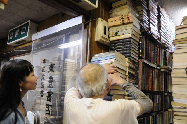 お客さんが「こんな本ありますか?」と聞くと、どんなに高く積まれた本の山の中からでも、お目当ての本を取り出してくれる。どの本がどこにあるのかは、店主のみぞ知る=今村優莉撮影