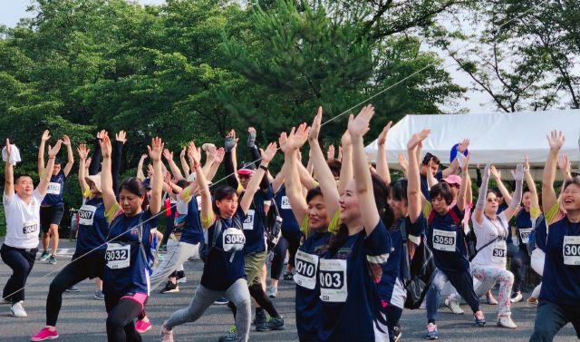 走る前にウォーミングアップの体操をする参加者たち