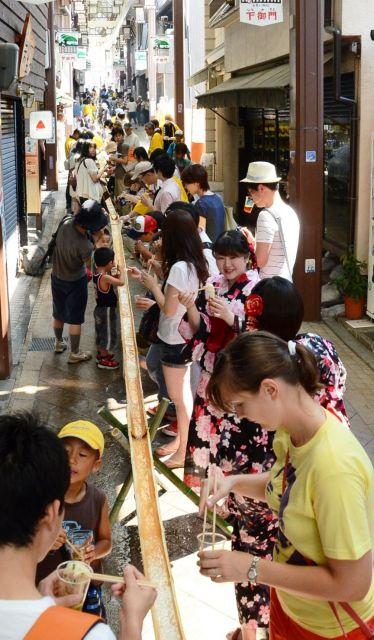 流しそうめんを楽しむ人たち=2012年7月、奈良市の下御門商店街