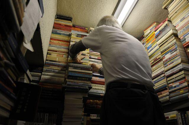 リクエストした文化大革命の本を取り出してくれる店主の簡木桂さん。一番高いところにあって心苦しく、自分でとろうとしたら「アンタには無理だよ。危ないからあちらに行ってなさい」と言って、脚立に乗って取ってくれた=今村優莉撮影