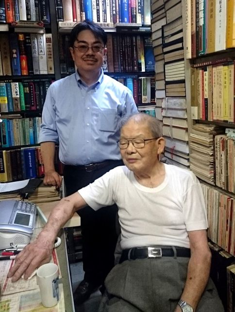 京都大の古勝隆一准教授(左)と東豊書店の店主簡木桂さん。その人柄と研究熱心さから、日本全国の研究者が、簡さんに電話してくるといいます。古勝さんは、電話口で話す簡さんの姿をよく覚えいているそうです。「津々浦々、研究者から本の問い合わせが来るんですが、単に本があるない、を教えるのではなく、こういう研究にはこういう本があるよ、と教えていました」=古勝さん提供