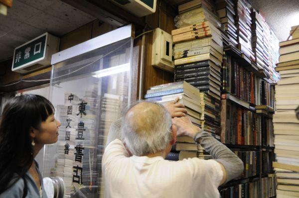 お客さんが「こんな本ありますか?」と聞くと、どんなに高く見えないところに積まれた本の山の中からでも、お目当ての本を取り出してくれる。どの本がどこにあるかは、店主のみぞ知る=今村優莉撮影