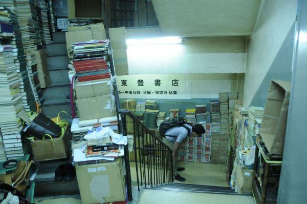 お店に入る前から、「書棚」はもうある。2階から3階に続く踊り場に山積みにされた書物。閉店前だからではなく、普段からこうなのだと、常連が教えてくれた=今村優莉撮影
