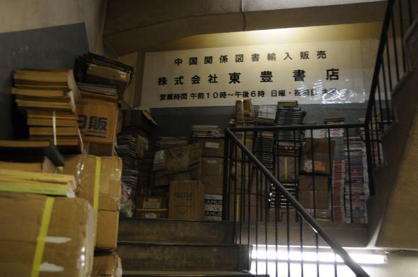 2階から3階に続く踊り場に山積みにされていた書物。一見しただけではどんなジャンルのものか分からない=今村優莉撮影