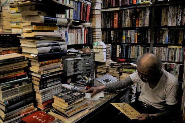 店主・簡木桂さんがすわる机の上にも、本が高く積まれていた=今村優莉撮影