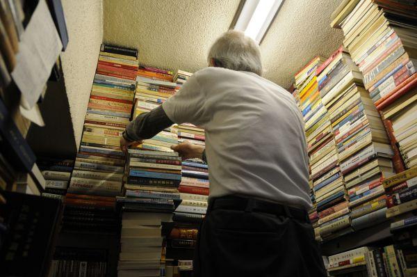 リクエストした文化大革命の本を取り出してくれる店主の簡木桂さん。一番高いところにあったので、脚立を使って自分で取ります、と申し出たら「あんたには無理だよ。危ないからあちらに行ってなさい」=今村優莉撮影