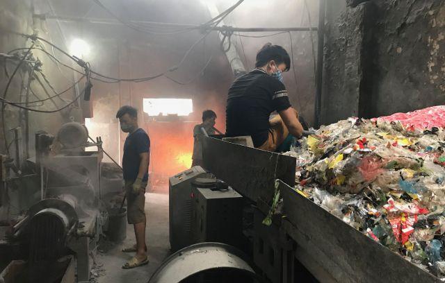 炉から煙がもくもく上がる中、作業をする人たち=鈴木暁子撮影