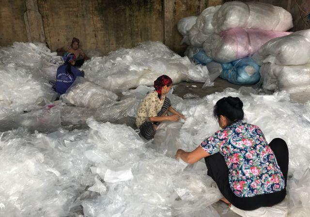プラスチックの大判シートを広げて丸める作業をする女性たち=ミンカイ村、鈴木暁子撮影