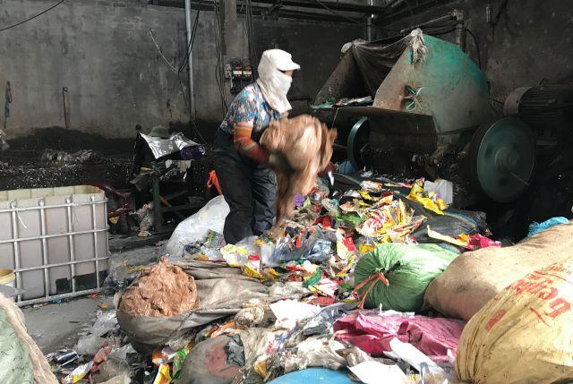 マスクをした女性が、すえたにおいのするプラスチックごみを機械に投入。まずは「洗浄」です=鈴木暁子撮影