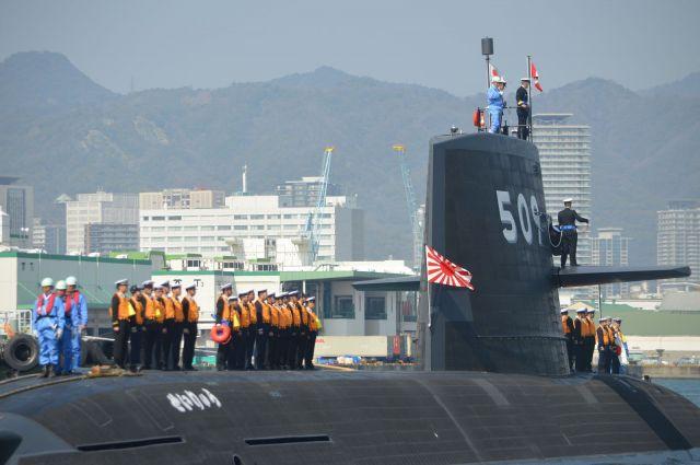 六甲の山並みと神戸の街を背に神戸港を発つ潜水艦せいりゅう=昨年3月、神戸市の三菱重工神戸造船所