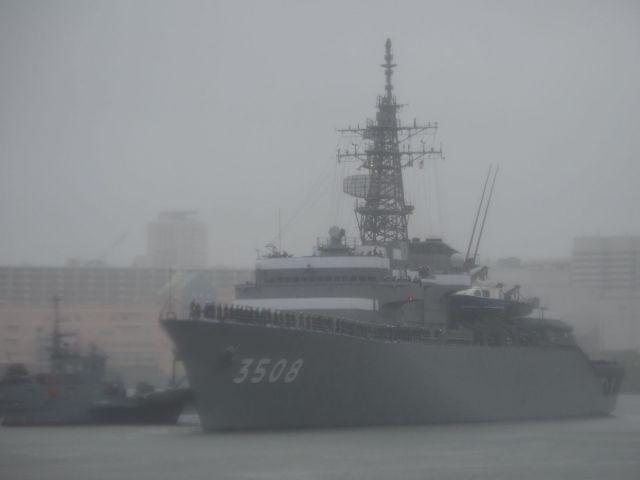 5月、風雨の中を遠洋航海に出る練習艦かしま。甲板に海自の幹部候補生らが立っている=神奈川県の横須賀港