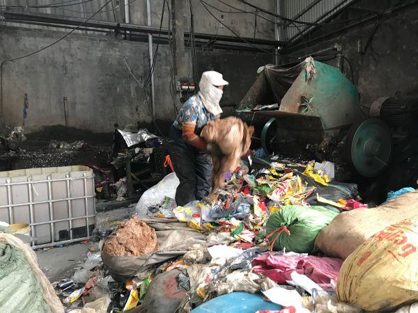プラスチックの再生作業場で、マスクをしてプラスチックを機械に投入する人=鈴木暁子撮影