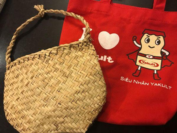 ベトナムの店でもらったかご袋とヤクルトのおまけの布袋=鈴木暁子撮影