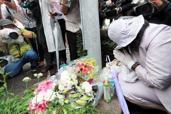 京都アニメーションの第1スタジオが見える場所に花をたむけ、手を合わせる女性=2019年7月19日、京都市伏見区、佐藤慈子撮影