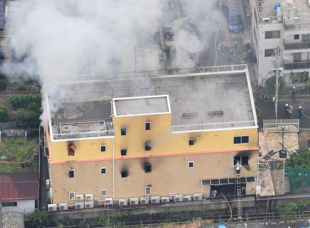 煙を上げて燃える京都アニメーションの建物。窓から炎が見える=2019年7月18日、京都市伏見区、朝日新聞社ヘリから、水野義則撮影