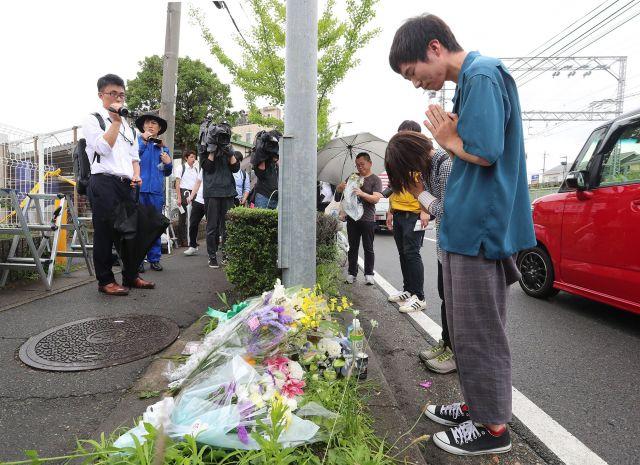 京都アニメーションのスタジオが見える場所で花を手向け、手を合わせる人たち=2019年7月19日、京都市伏見区、佐藤慈子撮影