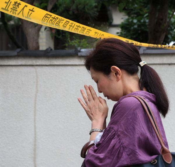 現場の近くで手を合わせる女性=2019年7月19日、京都市伏見区、内田光撮影