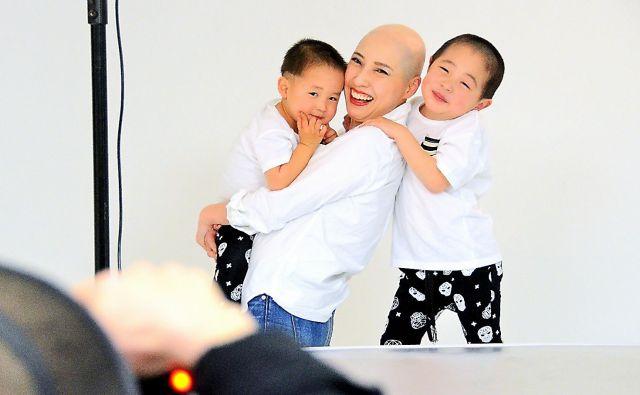 髪を失った女性たちの写真展のため、子どもと一緒に写真に収まる土屋さん