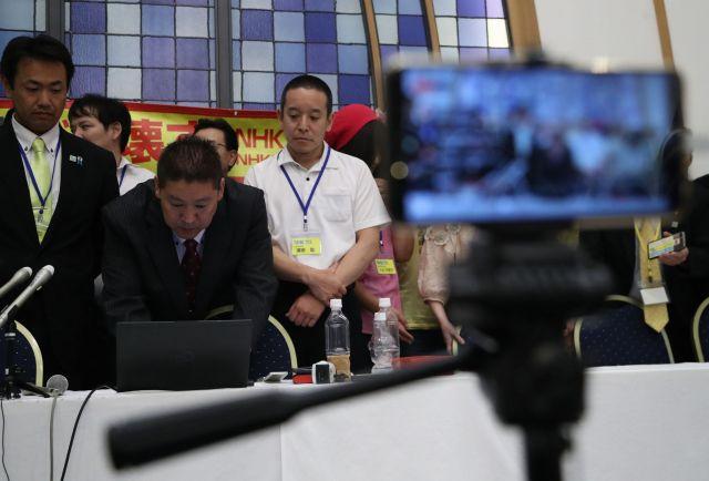 NHKから国民を守る党の参院選開票センターの様子は、ステージ前に置いたスマホで中継された。左から2人目は立花孝志代表=7月22日午前4時12分、東京都港区