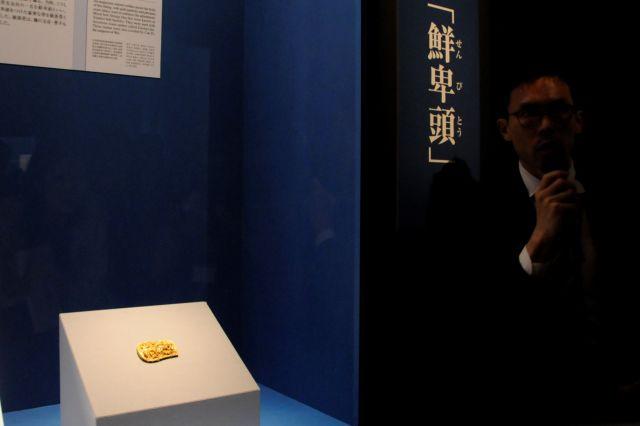 金製獣文帯金具(きんせいじゅうもんおびかなぐ、後漢時代・2世紀 寿県博物館蔵)。まばゆいばかりの金のベルトのバックルのそばで解説する東京国立博物館主任研究員の市元塁さん=今村優莉撮影