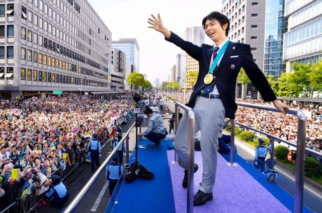 五輪2大会連続金メダルを祝福するパレードでファンに手を振る羽生結弦=2018年4月