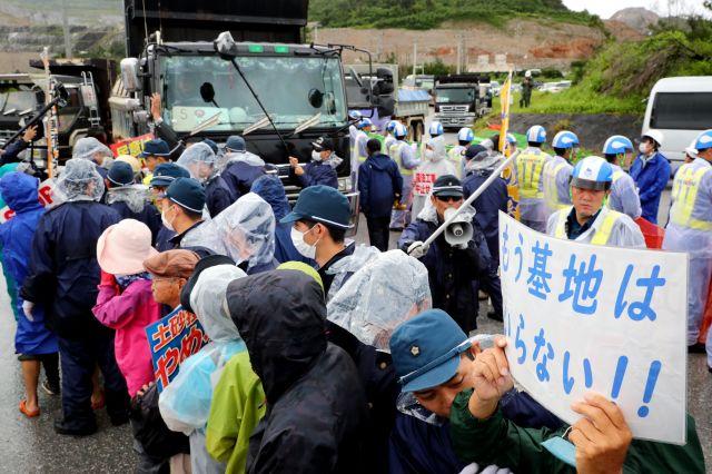 沖縄県本部町で港に入る工事車両の前で抗議する人たち=2019年6月24日、小宮路勝撮影