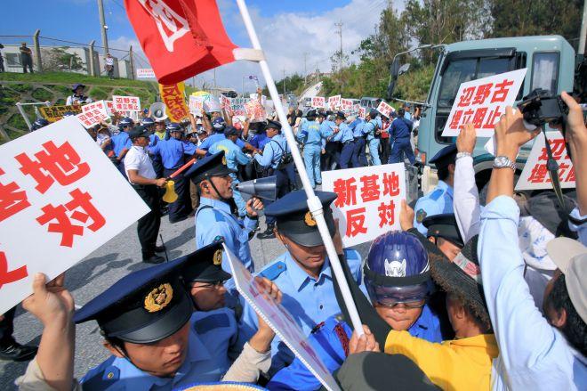 反対派と賛成派がネット上で意見を戦わせる沖縄の基地問題。写真は、米軍キャンプ・シュワブのゲート前にで、工事車両の進入を阻止しようと警察官や警備員らと激しくもみあう反対派住民=2014年8月14日、沖縄県名護市、藤脇正真撮影