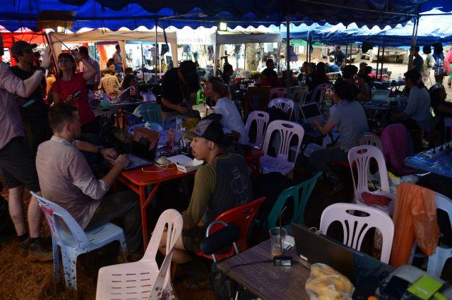 洞窟前の空き地には所狭しと机や椅子が並べられ、にわか作りの「プレスセンター」ができた=2018年7月、タイ北部メーサイ