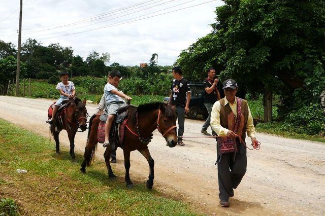 洞窟近くの道では、馬に乗って移動できる観光客用サービスも。子どもたちがうれしそうに乗っていた=2019年7月、タイ北部メーサイ