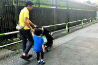 長男の手を引き、次男をベビーカーに乗せて保育園から帰る吉川記者