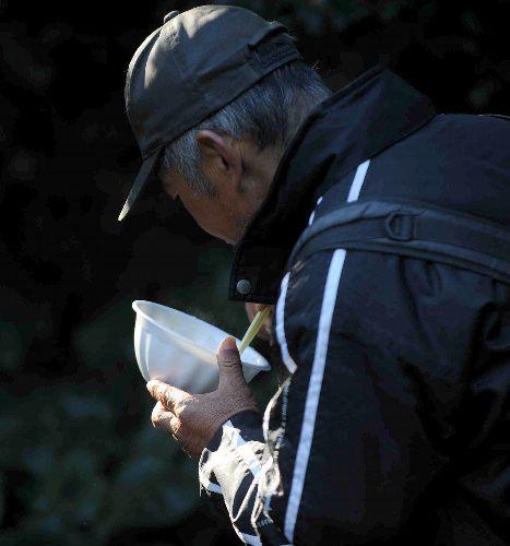 吐く息が白くなるほど冷え込んだ朝、入村者は、炊き出しの汁物の食事で暖をとった=2009年1月4日、遠藤真梨撮影