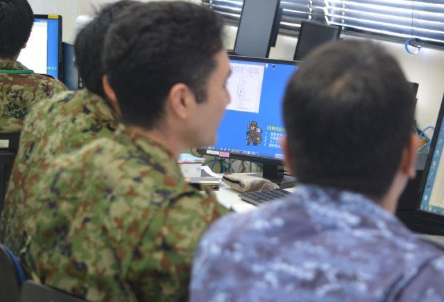 陸上自衛隊通信学校でのサイバー攻撃対処実習で、同じチームで相談する陸自と海自(右端)の隊員ら=8月2日。藤田撮影(以下同じ)
