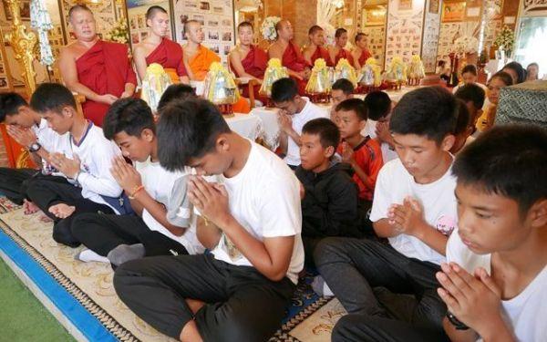 亡くなったダイバーの遺影に手を合わせる少年たち=2019年7月、タイ北部メーサイ