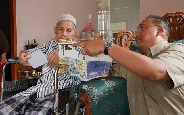 ザフラニ・アルフィンさん(右)から日本の書籍の写真を見せられながら、当時を思い出すオマール・ビンセニックさん=2019年8月、マレーシア・コタバル