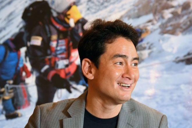 ヒマラヤ登山の写真を背景に、経験を語る野口健さん=8月9日、東京都渋谷区、迫和義撮影