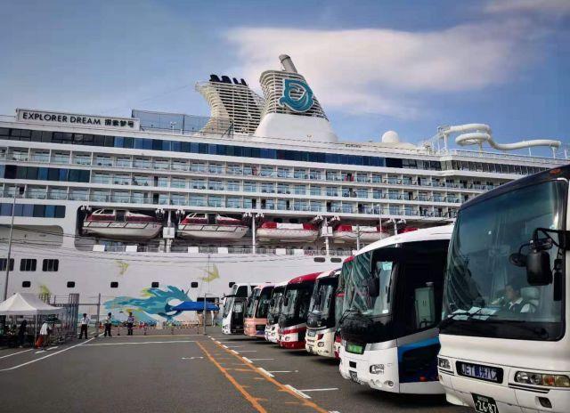 巨大クルーズ船と、ずらりと並ぶ観光客を待つバス