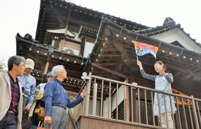 大漁旗で客を送り出す、「つなかん」女将の菅野さん=東野真和撮影