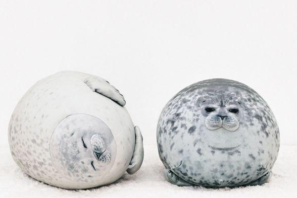 のほほん笑顔が魅力のアラレのクッション(左)と、「丸すぎるアザラシ」として話題になったユキを再現したクッション(右)