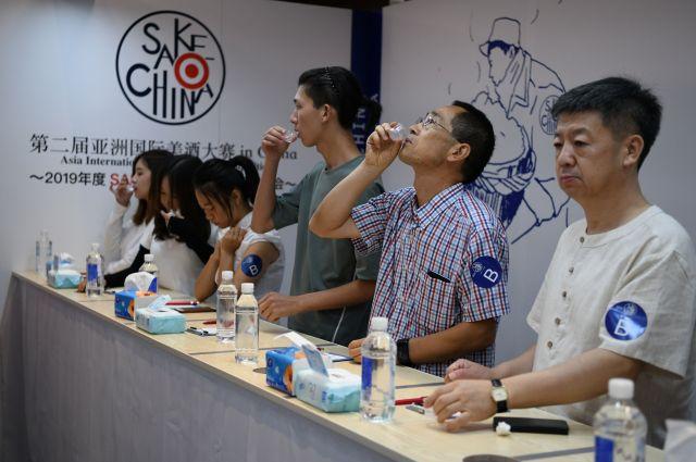 真剣な表情で日本酒を評価する参加者たち=冨名腰隆撮影