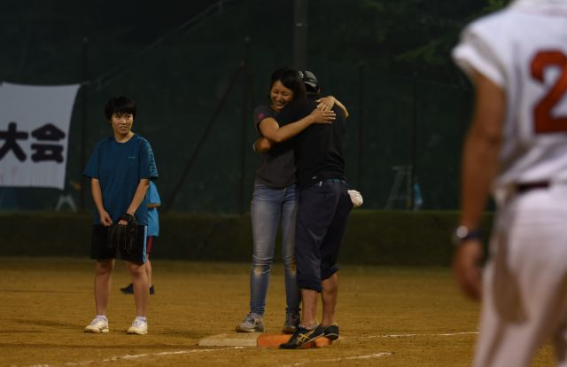 走塁中に転んだ妻を心配し、夫の主審と抱き合う場面もあった=岐阜県下呂市