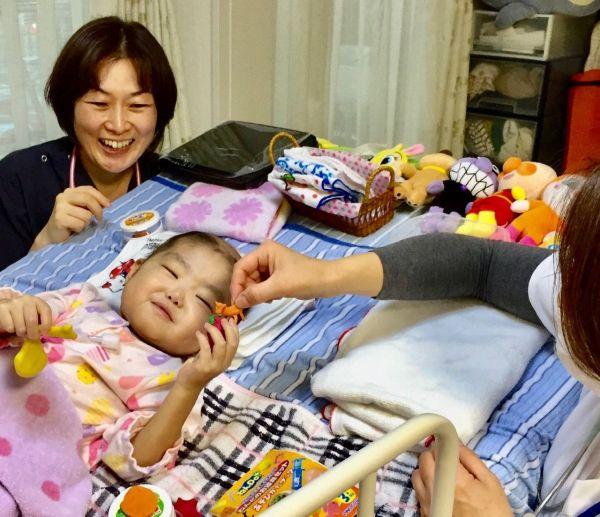 2018年11月19日、手のリハビリの一環で、粘土遊びをする侑花ちゃんと在宅医の森尚子さんや看護師(添田さん提供)