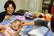 2018年11月19日、手のリハビリの一環で、粘土遊びをする侑花ちゃんと在宅医の森尚子さんや看護師=添田さん提供